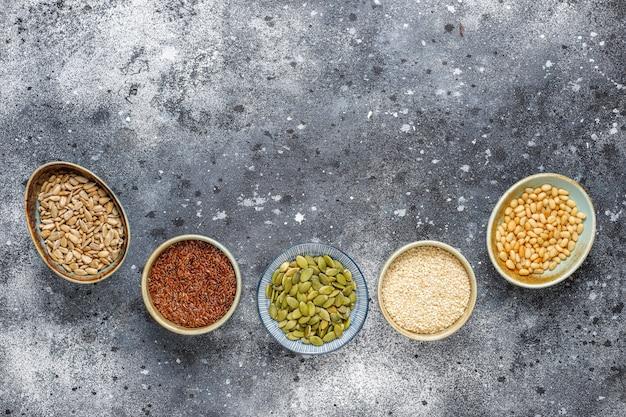 Verschiedene samen - sesam, leinsamen, sonnenblumenkerne, kürbiskerne für salate. Kostenlose Fotos
