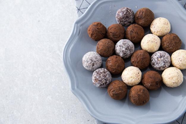 Verschiedene schokoladentrüffel mit kakaopulver, kokosnuss und gehackten haselnüssen auf einem dessertteller Premium Fotos