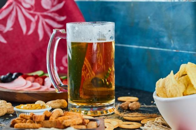 Verschiedene snacks, pommes, ein teller mit würstchen und ein glas bier auf dunkler oberfläche. Kostenlose Fotos