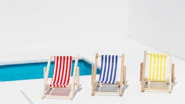 Verschiedene sonnenliegen neben sauberem pool Kostenlose Fotos