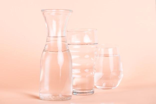 Verschiedene sortierte gläser mit wasser- und pfirsichhintergrund Kostenlose Fotos