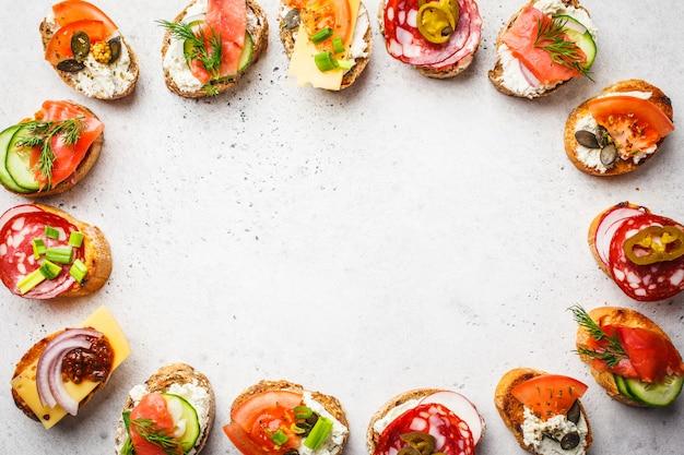 Verschiedene spanische tapas mit fisch, wurst, käse und gemüse. weißer hintergrund, draufsicht. Premium Fotos