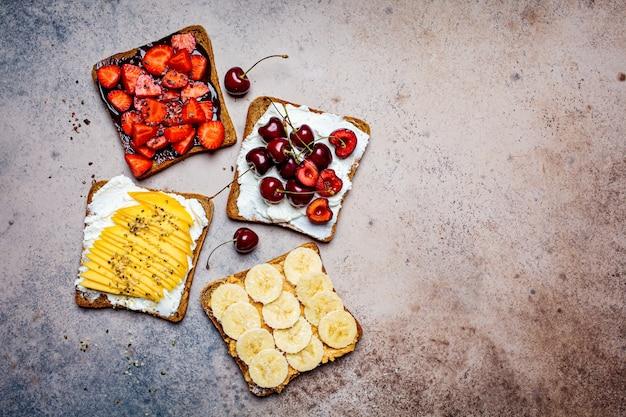 Verschiedene süße frucht toasts mit banane, mango, kirsche und erdbeeren auf dunklem hintergrund, draufsicht, kopienraum. Premium Fotos
