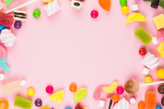 Verschiedene süße süßigkeiten, die rahmen auf rosa hintergrund bilden Premium Fotos