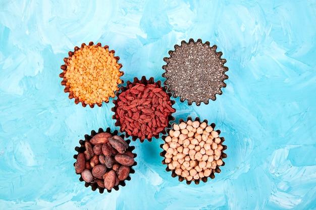 Verschiedene superfoods in der kleinen schüssel auf blau Premium Fotos