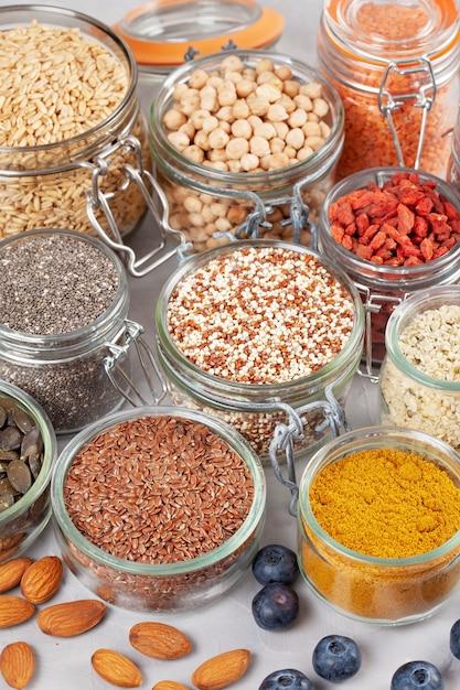 Verschiedene superfoods wie goji-beeren, quinoa, chia, hanfsamen, leinsamen, kichererbsen, hafer, mandeln, heidelbeeren, kurkuma, matcha und lantillen. diät-bioproduktkonzept des strengen vegetariers, der vegetarischen gesunden ernährung Premium Fotos