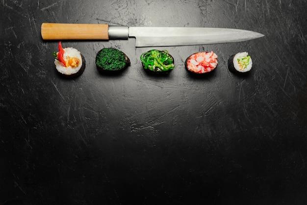 Verschiedene sushi mit japanischem messer auf schwarzem steinschieferhintergrund. sushi auf einem tisch. Kostenlose Fotos
