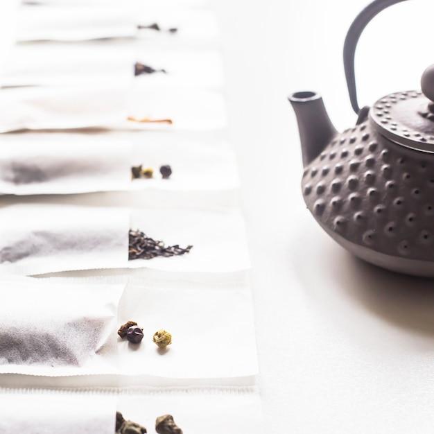 Verschiedene tees in einem wegwerffilterbeutel für das brauen nahe bei einem grauen roheisenkessel auf einem weißen hintergrund Premium Fotos