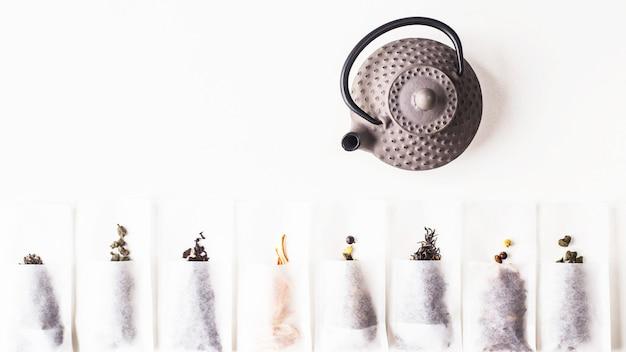 Verschiedene tees in einwegfilterbeuteln zum aufbrühen neben einem graugusskessel Premium Fotos