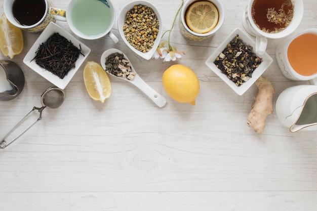 Verschiedene teesorten mit kräutern und trockenen blättern auf holztisch Kostenlose Fotos