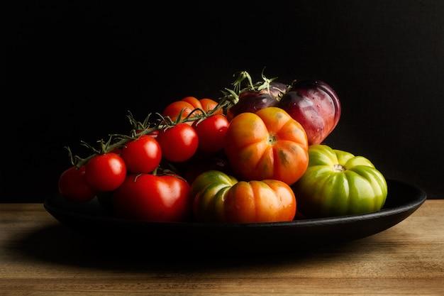 Verschiedene tomaten auf einem schwarzen teller auf einem holztisch Premium Fotos