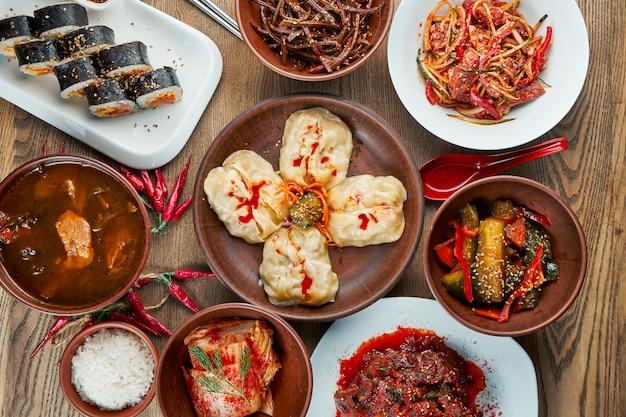 Verschiedene traditionelle koreanische gerichte - kimchi, gimbap-brötchen, gedämpfte knödel (mandu) auf einer holzoberfläche. draufsicht, flaches essen. koreanische küche Premium Fotos