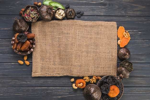 Verschiedene trockenfrüchte mit nüssen und leinwand Kostenlose Fotos