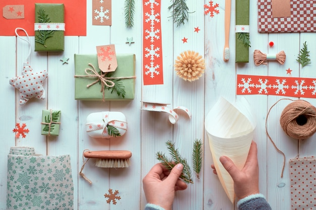 Verschiedene umweltfreundliche dekorationen für weihnachts- oder neujahrswinterferien, bastelpapierpakete und handgefertigte geschenke ohne abfall. flach lag auf holz, hände handgefertigte dekorationen mit grünen blättern. Premium Fotos