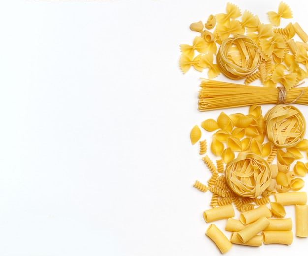 Verschiedene ungekochte nudeln. draufsicht. rohe nudeln mit zutaten zum kochen. lebensmittelkonzept Premium Fotos