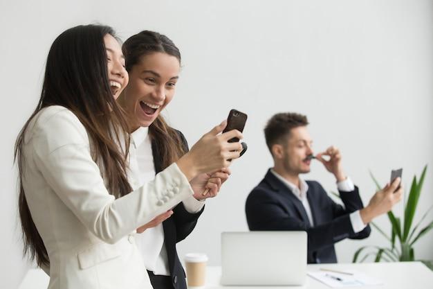 Verschiedene weibliche kollegen, die spaß mit smartphone im büro habend lachen Kostenlose Fotos