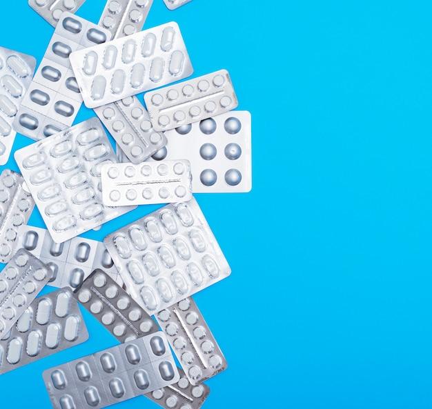 Verschiedene weiße tabletten in einer packung sind auf blau verstreut Premium Fotos