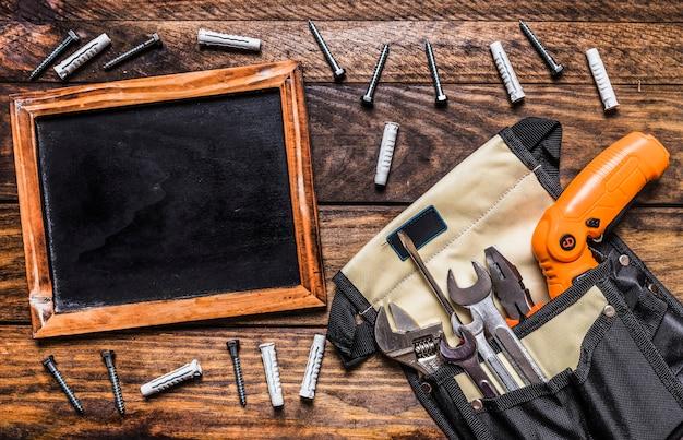 Verschiedene werkzeuge in toolbag nahe unbeschriebenem schiefer und schrauben auf hölzernem hintergrund Kostenlose Fotos