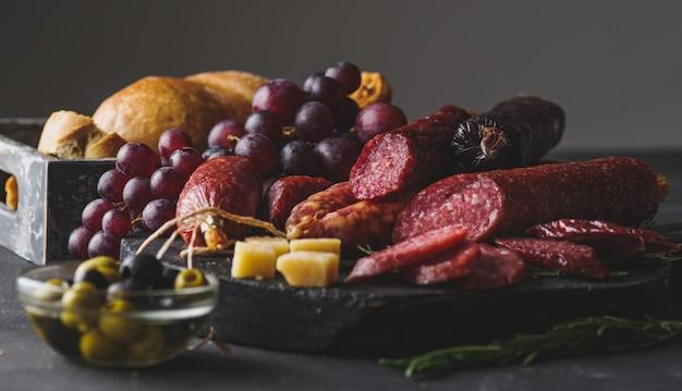 Verschiedene würste mit käse, trauben und oliven. geschnittene salami im rustikalen stil Premium Fotos