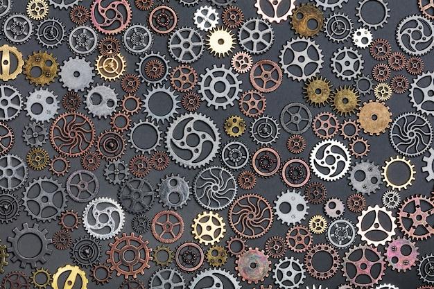 Verschiedene zahnräder, die auf grauen hintergrund legen. Premium Fotos
