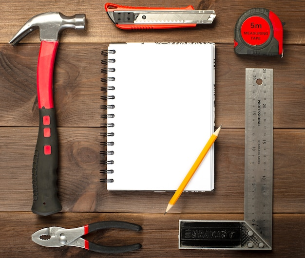 Verschiedene zimmerei, reparaturwerkzeuge, notizblock auf holz Premium Fotos