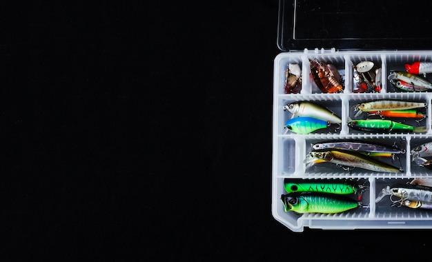 Verschiedener bunter fischereiköderkasten auf schwarzem hintergrund Kostenlose Fotos