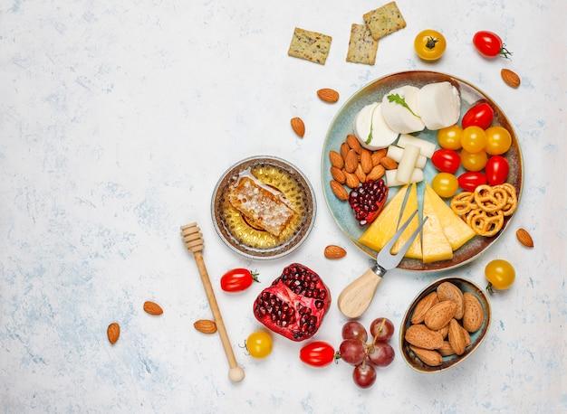 Verschiedener käse und käseplatte auf leuchtpult mit verschiedenen nüssen und früchten Kostenlose Fotos