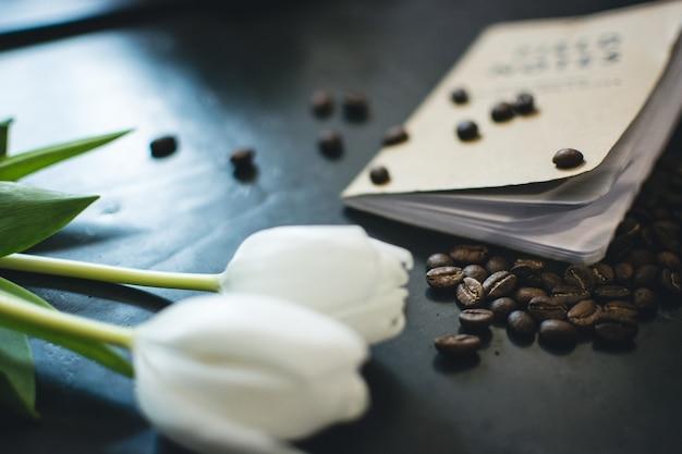 Verschüttete kaffeebohnen, buch und tulpen Kostenlose Fotos