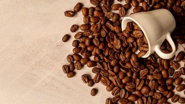 Verschüttete kaffeetasse mit gerösteten bohnen Kostenlose Fotos