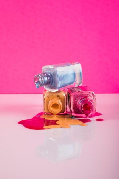 Verschütteter nagellack getrennt auf rosafarbenem hintergrund Kostenlose Fotos