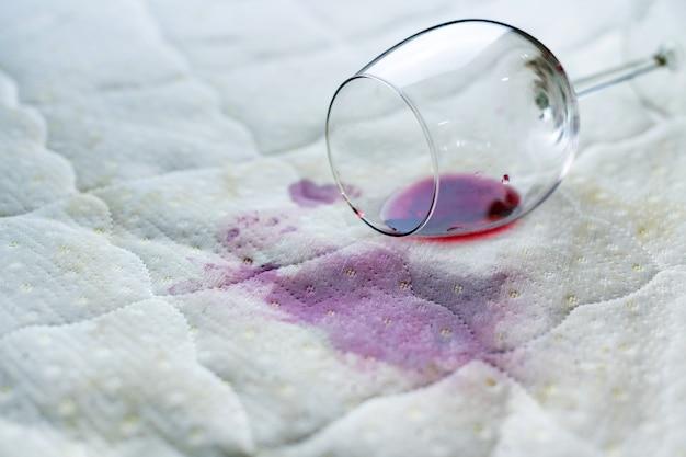 Verschüttetes weinglas auf dem bett. versehentlich fallen gelassenes weinglas auf weißem bettlaken Premium Fotos