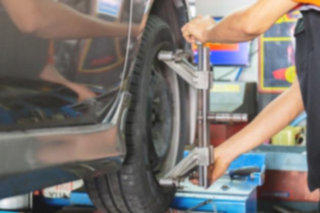 Verschwommen vom mechaniker, der die achsmessvorrichtung auf einem autorad fixiert Premium Fotos