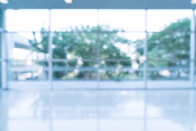 Verschwommene abstrakte hintergrund innenansicht blick auf in richtung zu leeren büro lobby und eingangstüren und glas vorhang wand mit rahmen Kostenlose Fotos