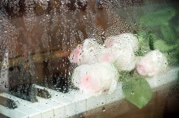 Verschwommenes bild durch nasses glas: hellrosa rosen liegen auf der klaviertastatur. Premium Fotos