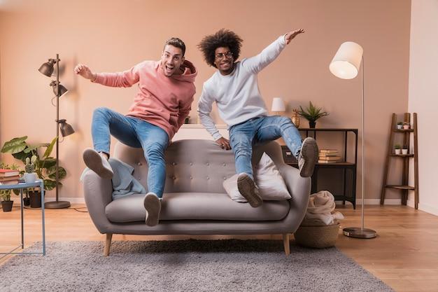 Verspielte freunde springen auf der couch Kostenlose Fotos