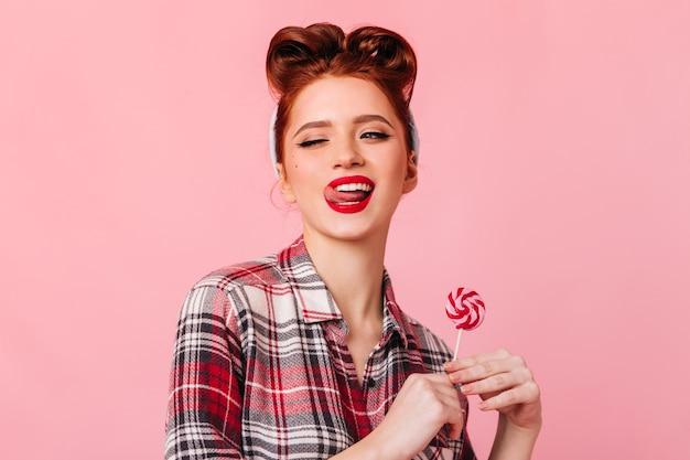 Verspielte junge frau im karierten hemd, das mit süßigkeit aufwirft. atemberaubendes pinup-mädchen, das auf rosa raum mit lutscher steht. Kostenlose Fotos