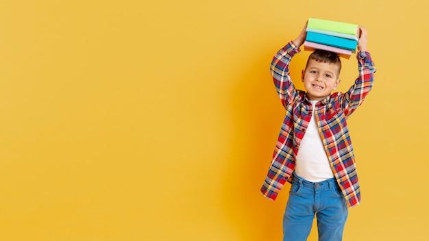 Verspielter junge mit einem stapel bücher auf seinem kopf Kostenlose Fotos