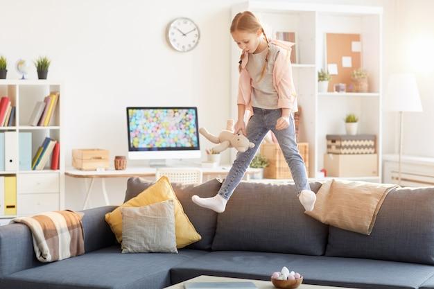 Verspieltes mädchen, das auf couch springt Premium Fotos