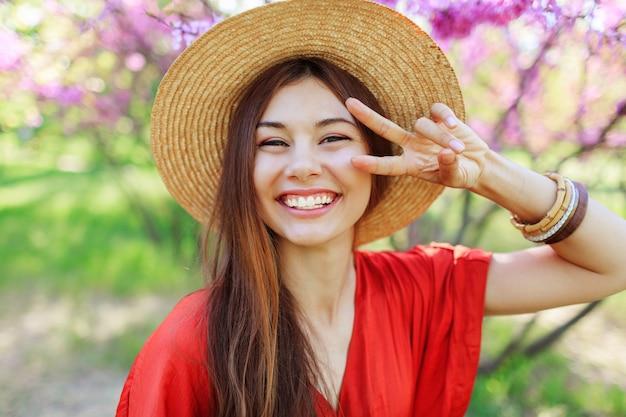 Verspieltes süßes mädchen, das lustiges gesicht macht und zeichen zeigt, im frühlingspark auf blühenden bäumen aufwirft Kostenlose Fotos