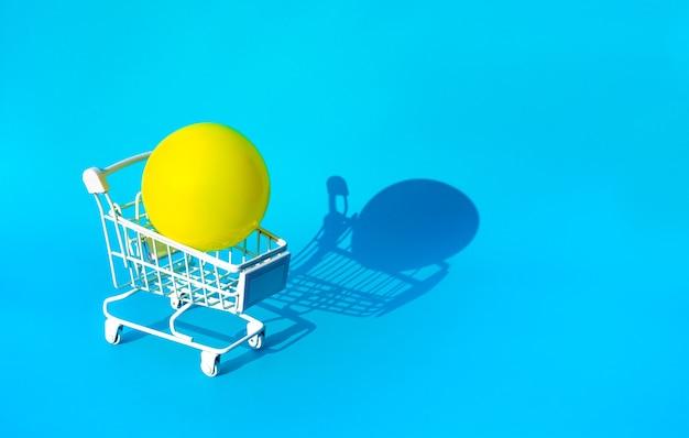 Verspotten sie den gelben ball auf carttrolley für supermarkt-einkaufskonzepte Premium Fotos