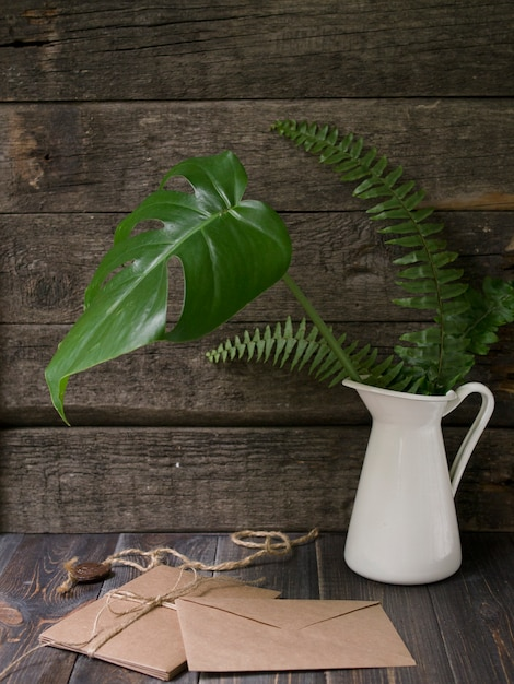 Verspotten sie herauf arbeitsplatz mit tropischen blättern in den vasen- und handwerksumschlägen auf hölzernem hintergrund Premium Fotos