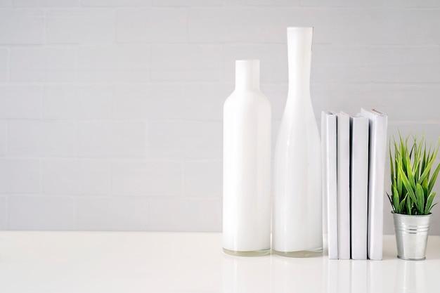 Verspotten sie herauf glasflasche, bücher und houseplant auf weißer tabelle mit weißer backsteinmauer Premium Fotos