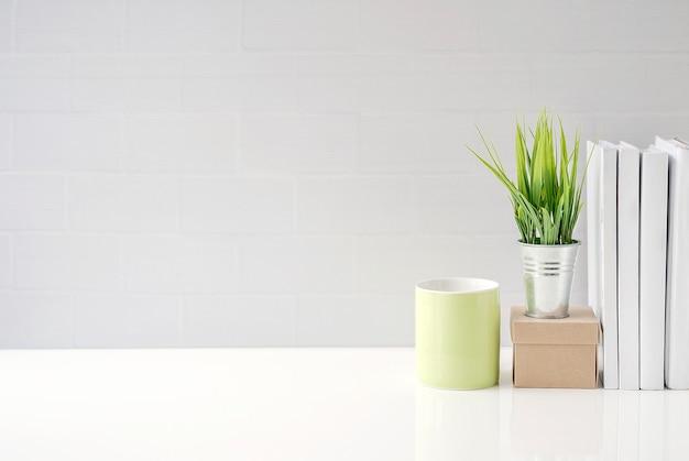 Verspotten sie herauf grünen becher, papierkasten, houseplant und bücher auf weißer tabelle mit weißer backsteinmauer Premium Fotos