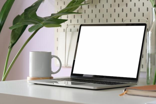 Verspotten sie herauf laptop des leeren bildschirms im dachbodenarbeitsplatz Premium Fotos
