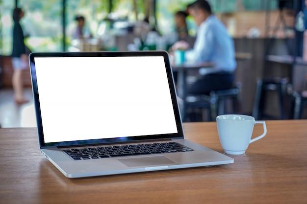 Verspotten sie oben unter verwendung des laptops mit dem modernen computer des leeren bildschirms Premium Fotos