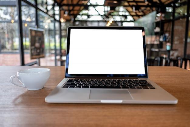 Verspotten sie sich mit laptop mit modernem arbeitsplatz des leeren bildschirms in der kaffeestube Premium Fotos