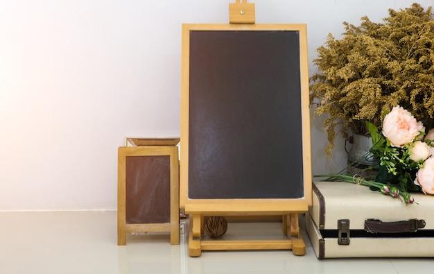 Verspotten sie von der leeren tafel oder von der tafel auf weißer wand und weinlesegegenstand. Premium Fotos