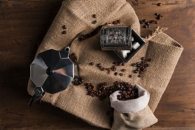 Verstreute bohnen aus sack in der nähe von kaffeemaschine und schachtel zucker Kostenlose Fotos