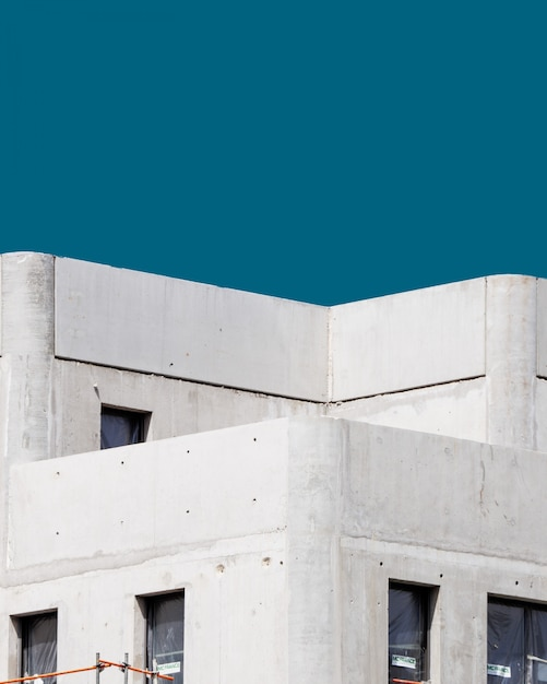 Vertikal eines weißen betongebäudes unter dem blauen himmel Kostenlose Fotos