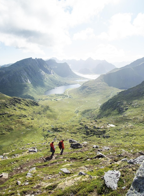 Vertikal von menschen, die in den bergen der lofoten bei bewölktem wetter wandern Kostenlose Fotos